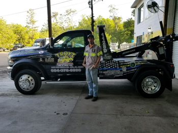 roadside assistance Troyz Towing & Storage driver standing in front of a heavy duty towing truck in Jacksonville, FL
